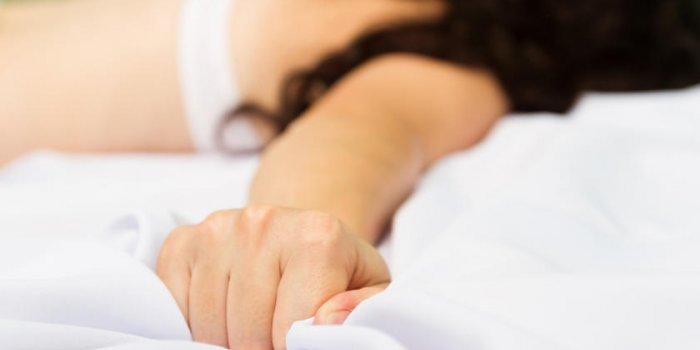 main féminine tirant des draps blancs en extase, l'orgasme