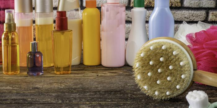many kind of shampoo and shower gel bottles and sponge on the table
