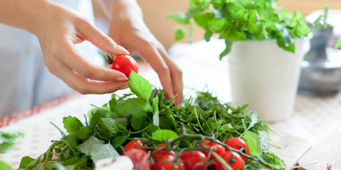 woman is cooking in home kitchen female hands choose cherry tomatoes, vegetables for recipe ingredients for preparing ita...