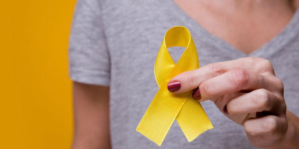 young female holding yellow gold ribbon awareness symbol for endometriosis, suicide prevention, sarcoma bone cancer, blad...
