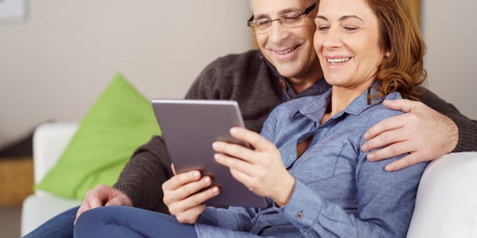 verliebtes paar sitzt auf dem sofa und schaut auf tablet