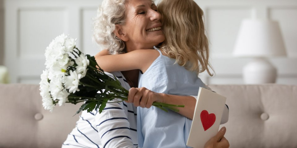 sincere old grandma hugs small attentive granddaughter express her gratitude for received surprise at birthday or 8-march...