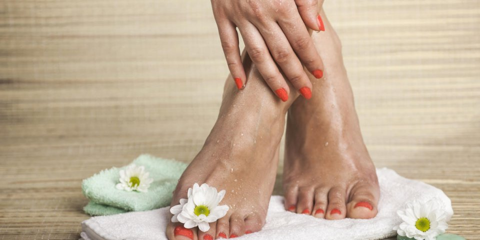 female feet and hand with drops of water, towel, flowers and spa rocks copy space