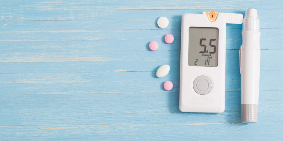 glucometer and pills on blue wooden background