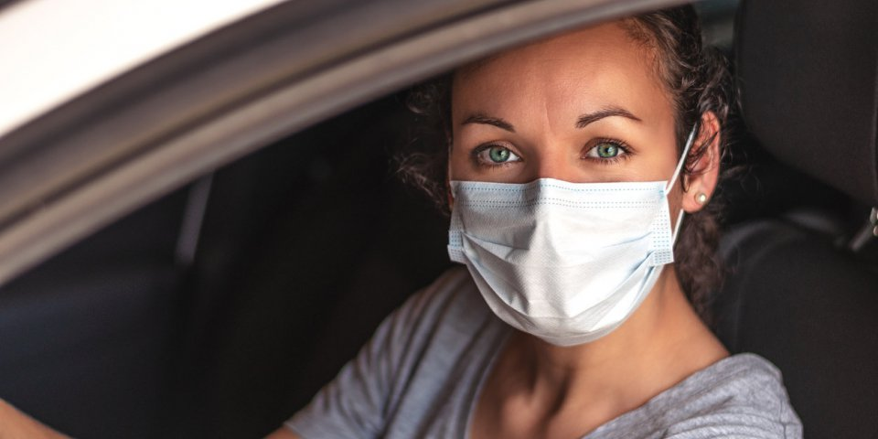 young woman driving car with protective mask on her face covid-19 coronavirus healthcare or allergy protection