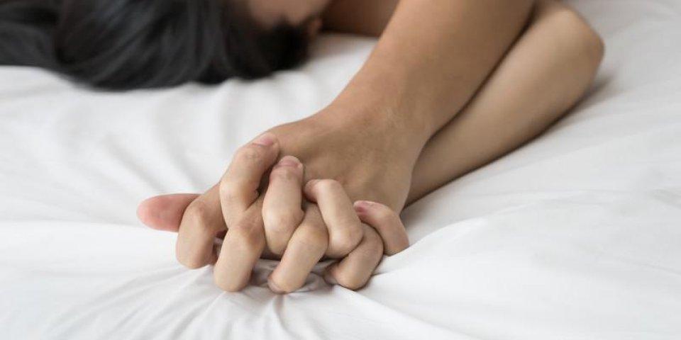 jeune couple faisant l'amour au lit se concentrer sur la main
