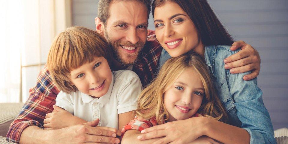 de beaux jeunes parents et leurs enfants se font des câlins, regardant la caméra et souriant tout en restant assis sur ...