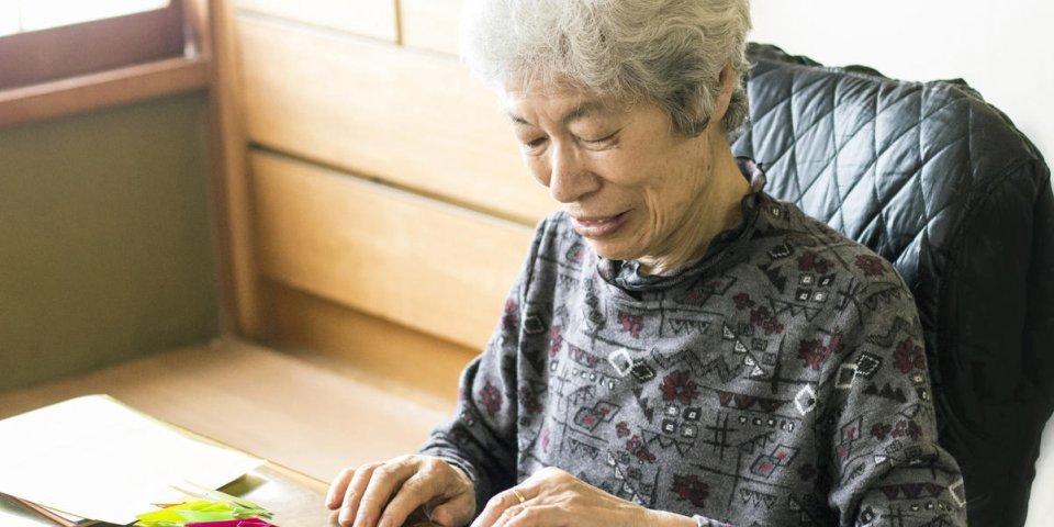 dame senior japonaise pliant des grues de papier à la maison