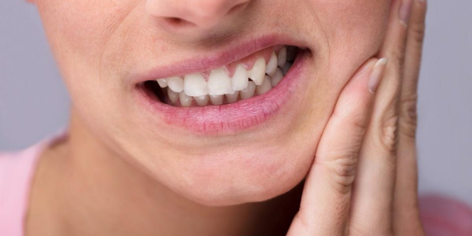 close-up of young woman suffering from toothache at home