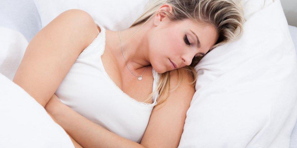 portrait de femme avec mal de ventre allongé sur le lit
