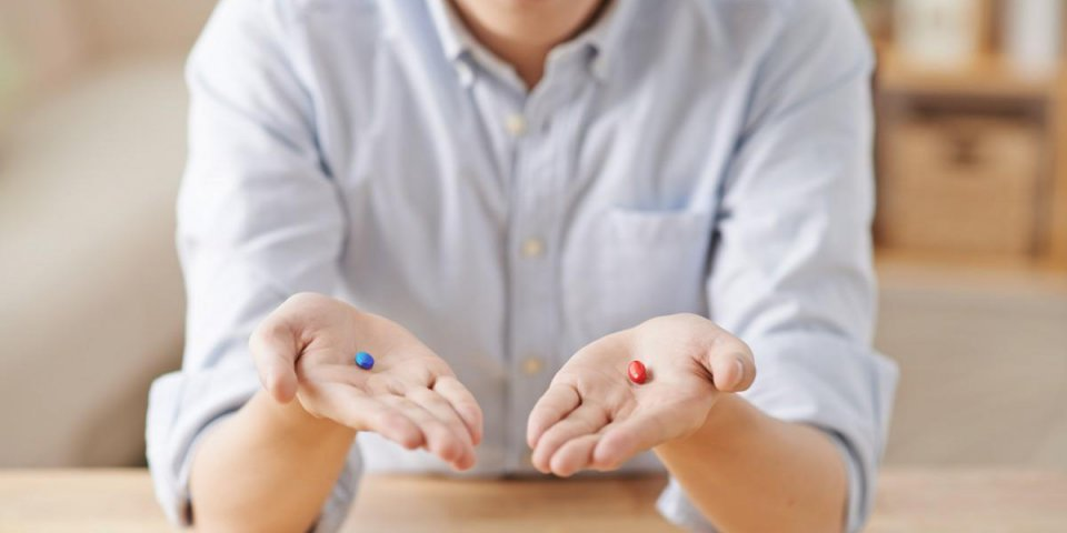 man offering you red and blue pills, selective focus