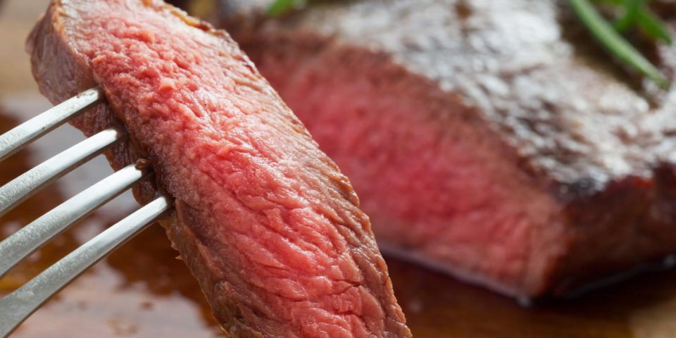 bifteck de faux-filet rôti moyen sur une assiette en bois avec du poivre et du sel