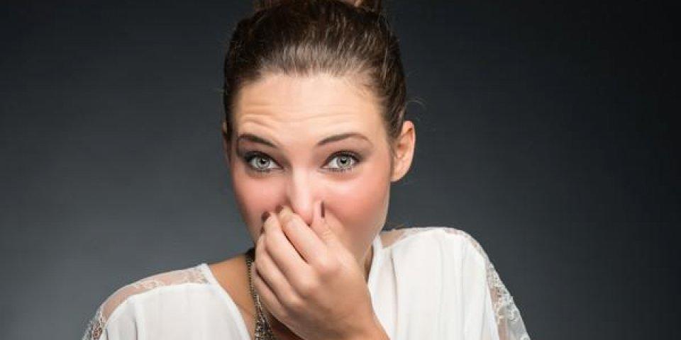 portrait d'une jeune femme tenant son nez à cause d'une mauvaise odeur isolée sur fond gris