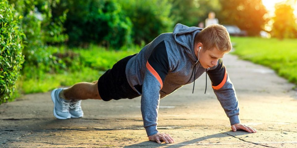 male athlete exercising in the park portrait of a male guy doing push-ups the concept of a healthy lifestyle strength and...