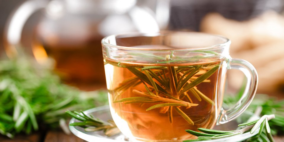 rosemary tea in glass tea cup on rustic wooden table closeup herbal vitamin tea