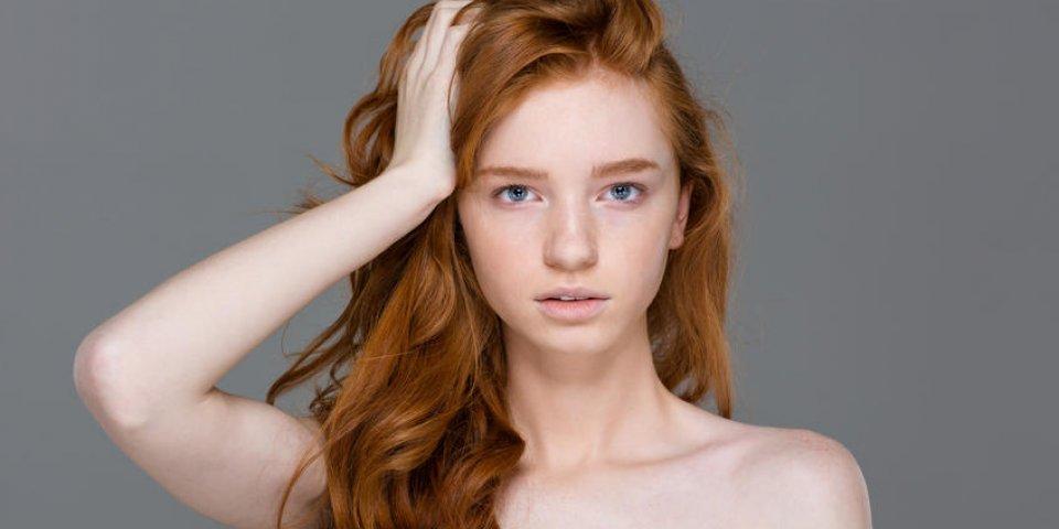 portrait de beauté de tendre jolie jeune femme avec de beaux longs cheveux roux sur fond gris