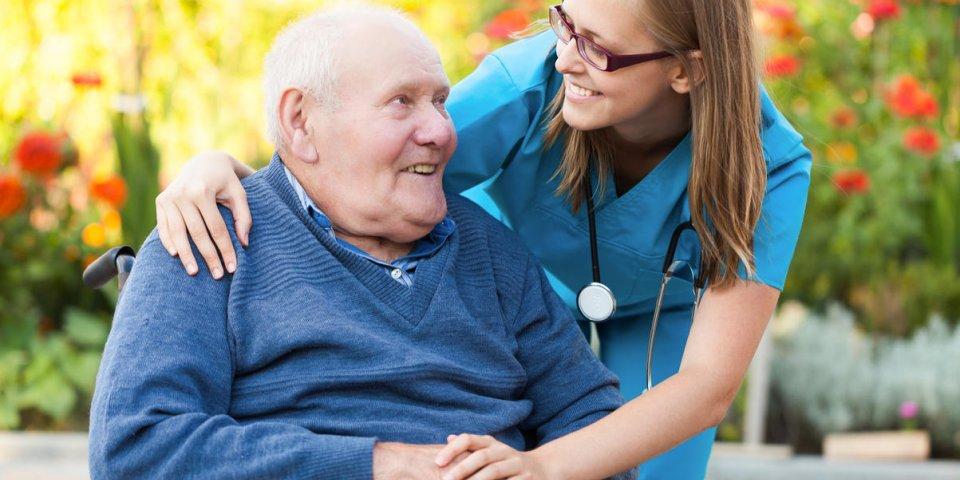 médecin gentil en prenant soin d'un vieil homme en fauteuil roulant