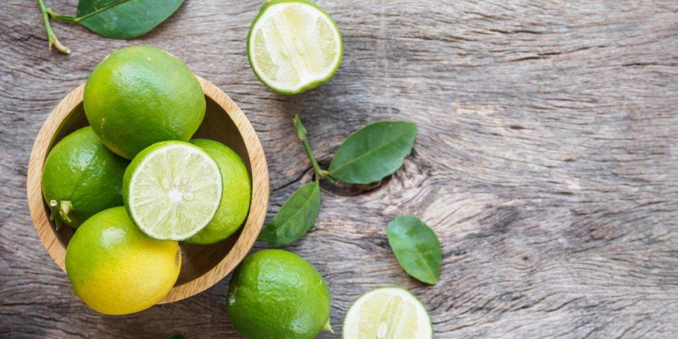 vue de dessus du groupe de citron vert et tranche dans un bol sur fond en bois avec espace copie