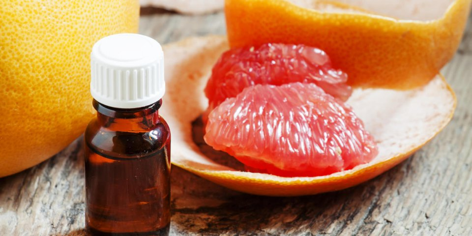 grapefruit essential oil in a small bottle and fresh grapefruit, selective focus