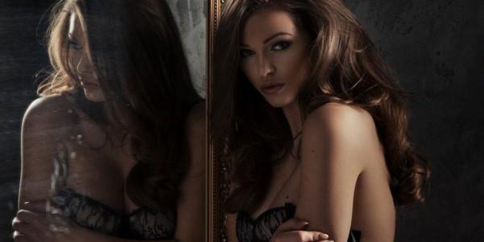 dame sexy en lingerie noire jouant avec elle-même à travers un miroir