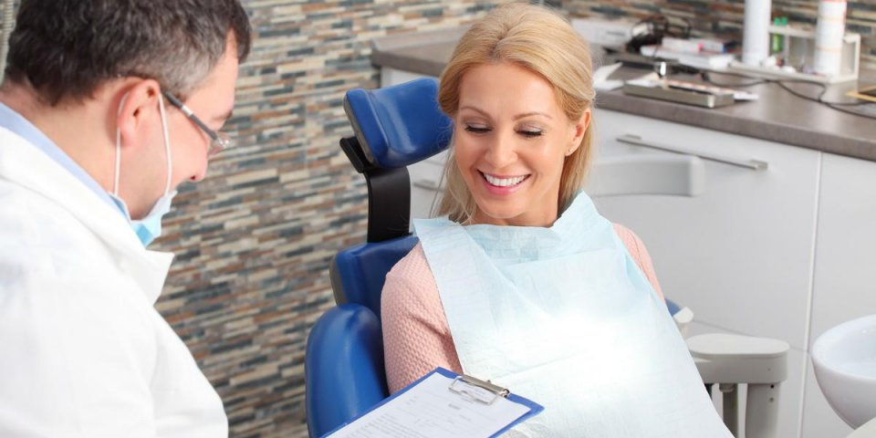 portrait of friendly male dentist holding in his hand a clipboard and consulting with his beautiful patient at dentist office