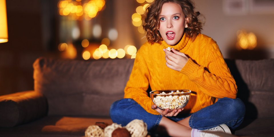 fascinated young female in sweater eating popcorn and watching interesting film on tv while sitting on couch in evening a...