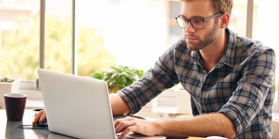 jeune homme avec des lunettes travaillant sur son carnet de notes, avec une tasse de café fraîche agréable et tôt le ...
