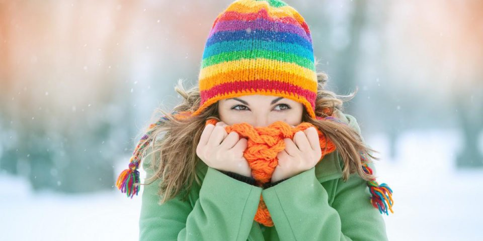 portrait of a young woman in snow with scarf on her face trying to warm herself winter concept