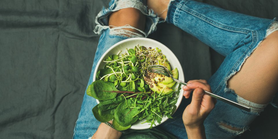green vegan breakfast meal in bowl with spinach, arugula, avocado, seeds and sprouts girl in jeans holding fork with knee...