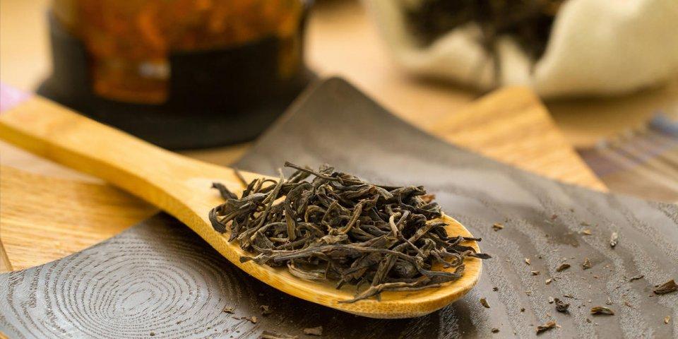 puerh de thé sec sur une cuillère en bois, théière et un sac de toile de jute en arrière-plan