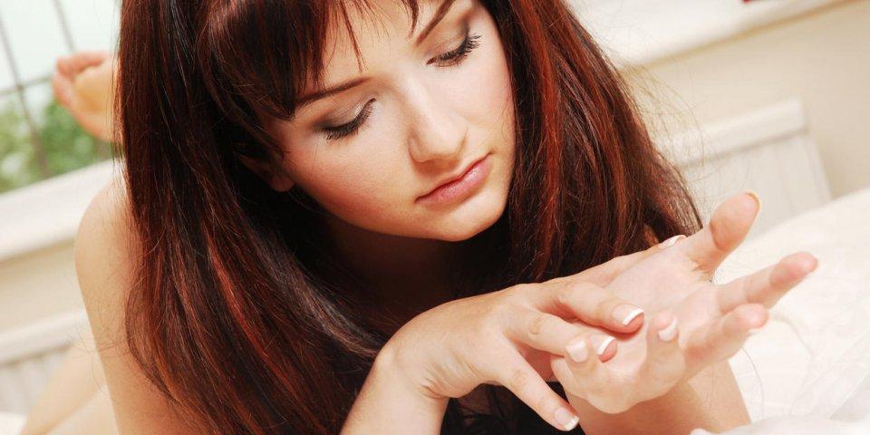 une belle jeune femme au lit en regardant ses mains