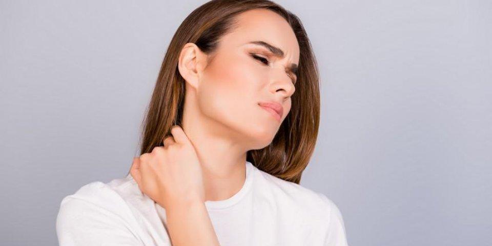 jeune femme aux cheveux bruns frustrés a une forte douleur au cou, elle est dans un tshirt blanc, masser le cou, avec la...