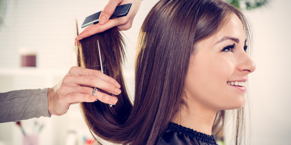young beautiful woman having her hair cut at the hairdresser's