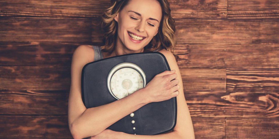 beautiful young woman in sportswear is hugging weigh scales and smiling, on wooden background
