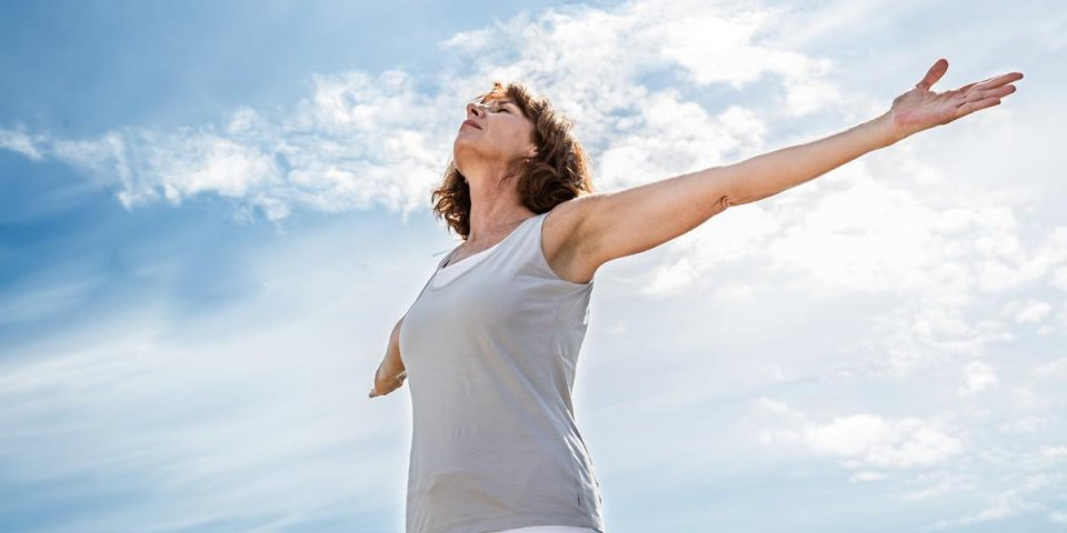 breathing outside - zen middle aged yoga woman opening up her chakra with arms raised,practicing meditation for freedom o...