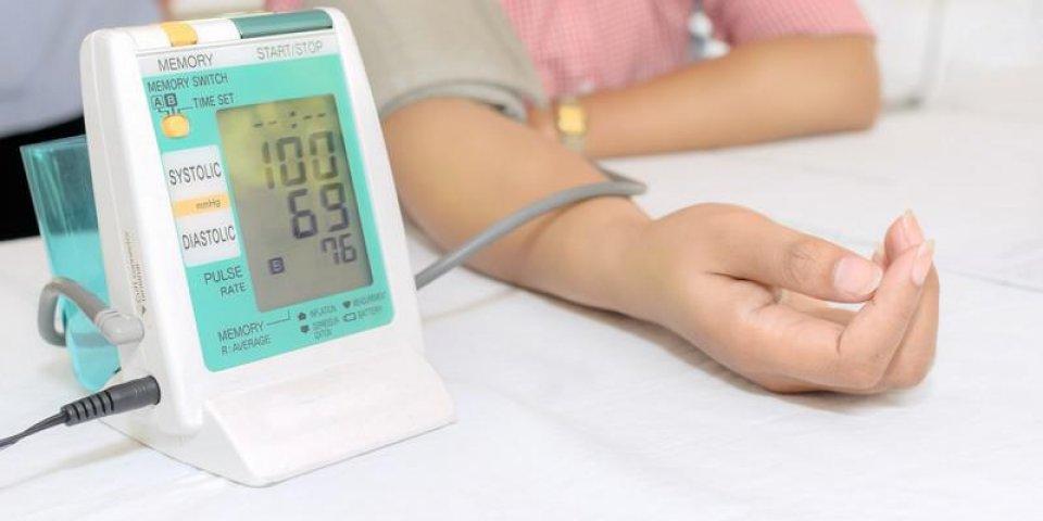 une femme mesurant sa tension artérielle en utilisant un tensiomètre numérique