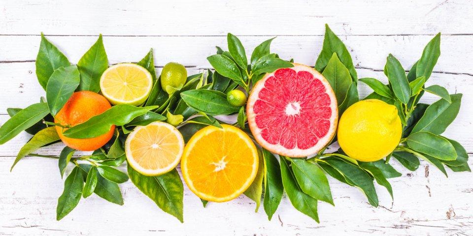 fresh citrus fruits on white wood background
