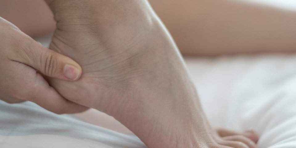 heel pain or plantar fasciitis concept hand on foot as suffer from inflammation feet problem of sever's disease or calcan...