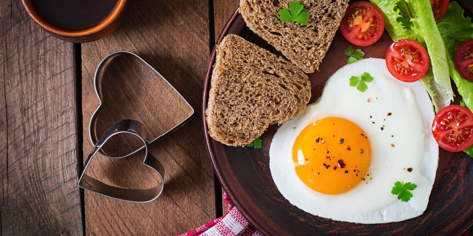breakfast on valentine's day - fried eggs and bread in the shape of a heart and fresh vegetables top view