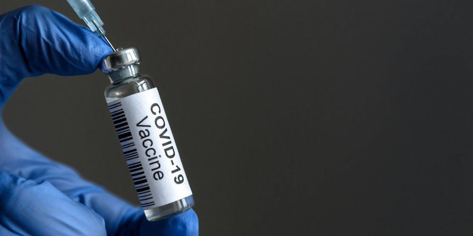 covid-19 vaccine bottle and syringe for coronavirus cure in doctor's hand for background concept of corona virus treatm...
