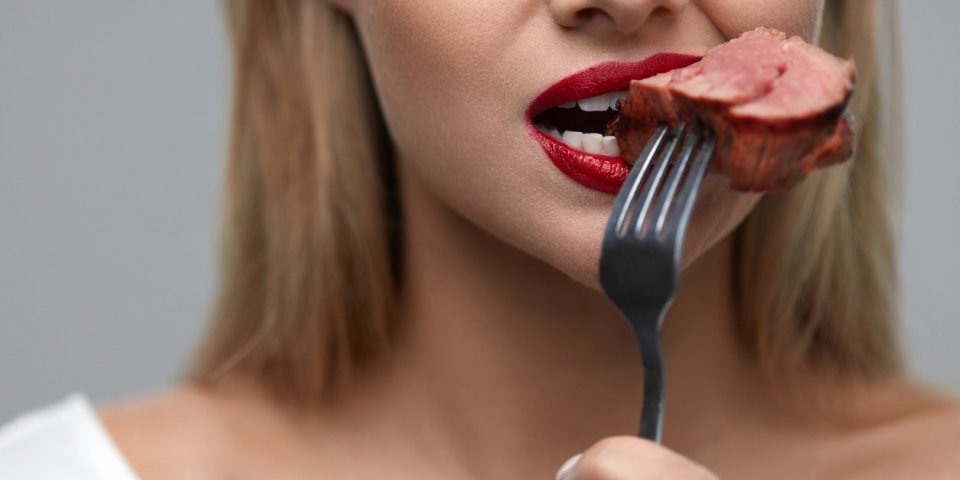 woman eating meat closeup of healthy hungry girl with beautiful face, red lips eats delicious grilled meat female mouth b...