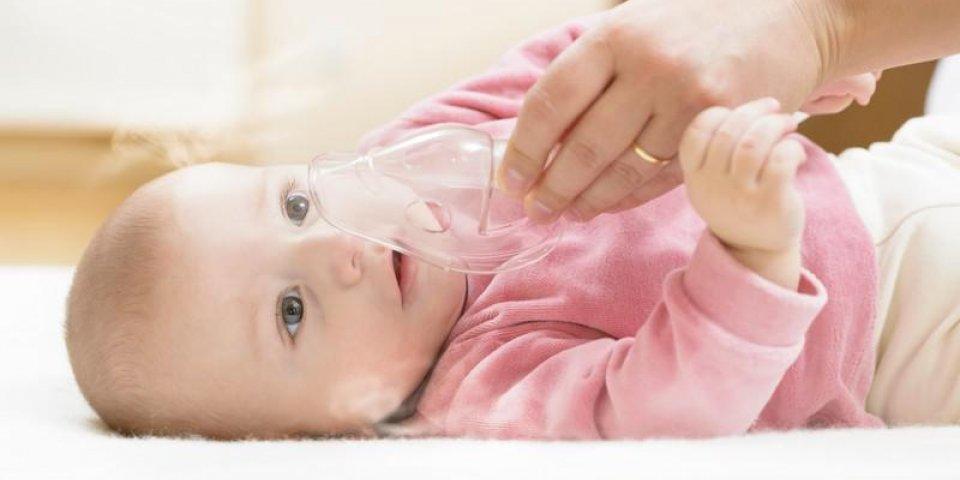 bébé prenant la thérapie respiratoire main tenant le masque d'un nébuliseur