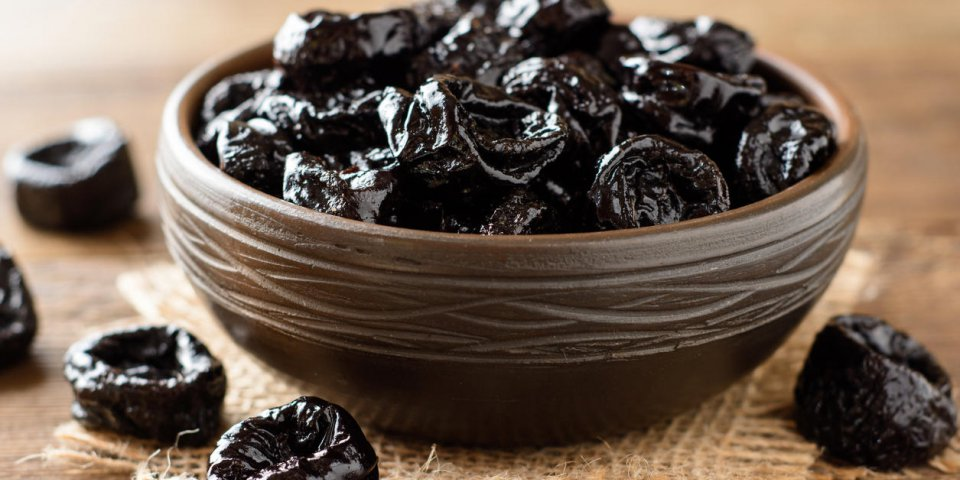 prunes in ceramic bowl on rustic wooden table dried plums selective focus