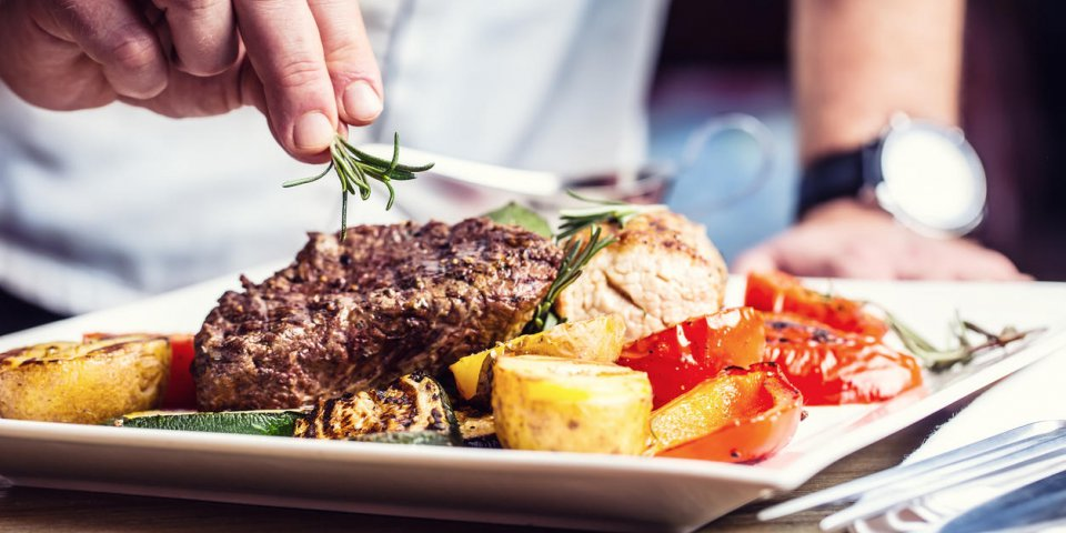 chef in hotel or restaurant kitchen cooking only hands prepared beef steak with vegetable decorationchef in hotel or rest...