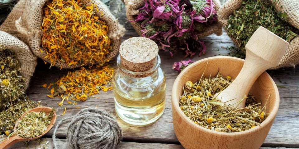 healing herbs in hessian bags, mortar with chamomile and essential oil on wooden table, herbal medicine