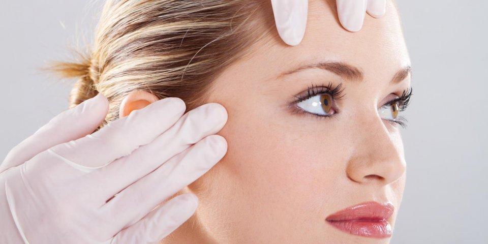 gros plan du médecin effectuer une vérification de la peau avant la chirurgie plastique