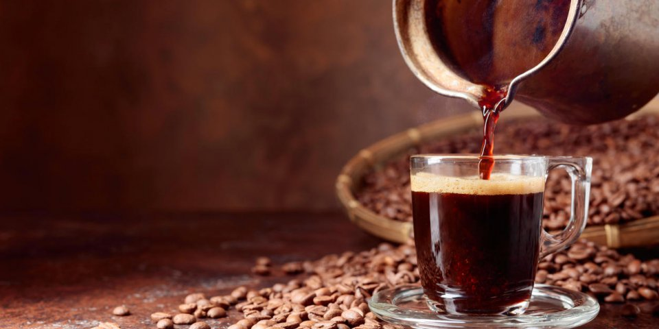 black coffee is poured into a small glass cup from a old copper coffee maker copy space
