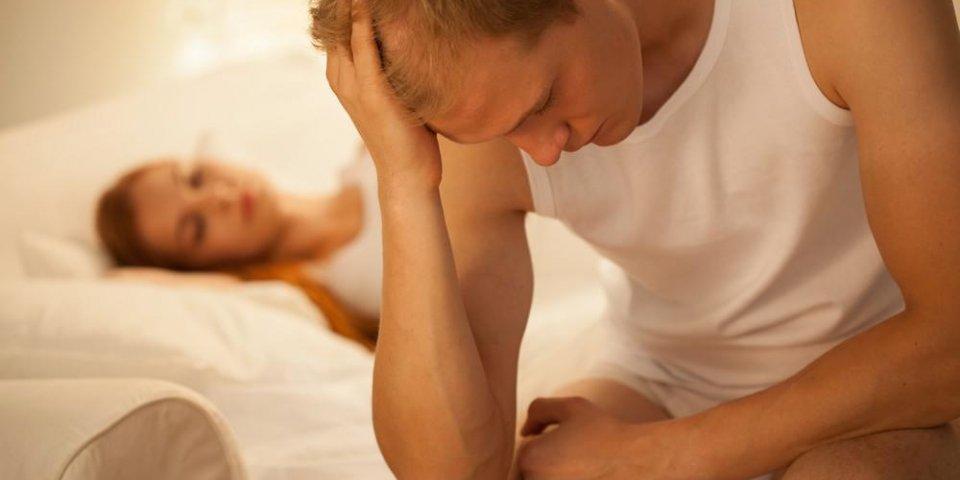 jeune homme inquiet assis dans son lit