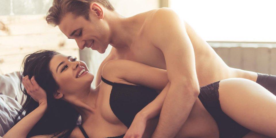beau jeune couple se regarde et souriant tout en ayant des relations sexuelles sur le lit