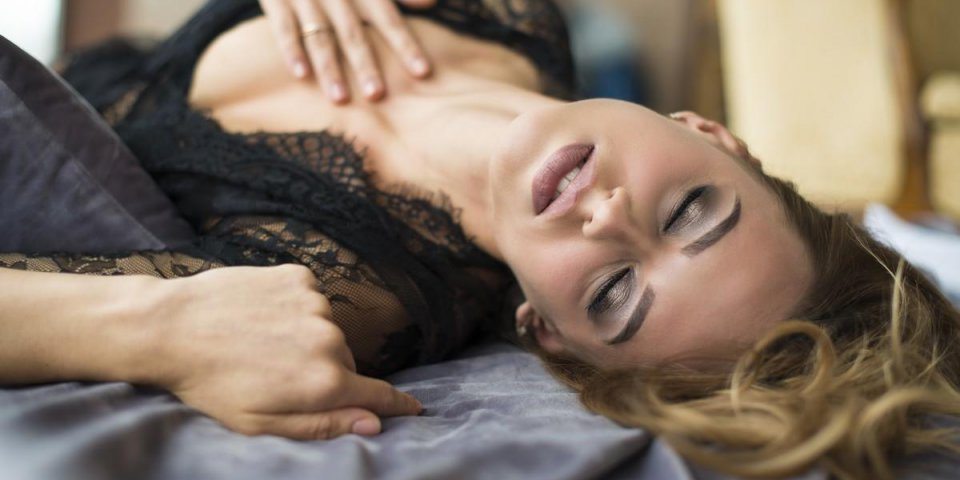 view of sensual girl in black lace lying in bed